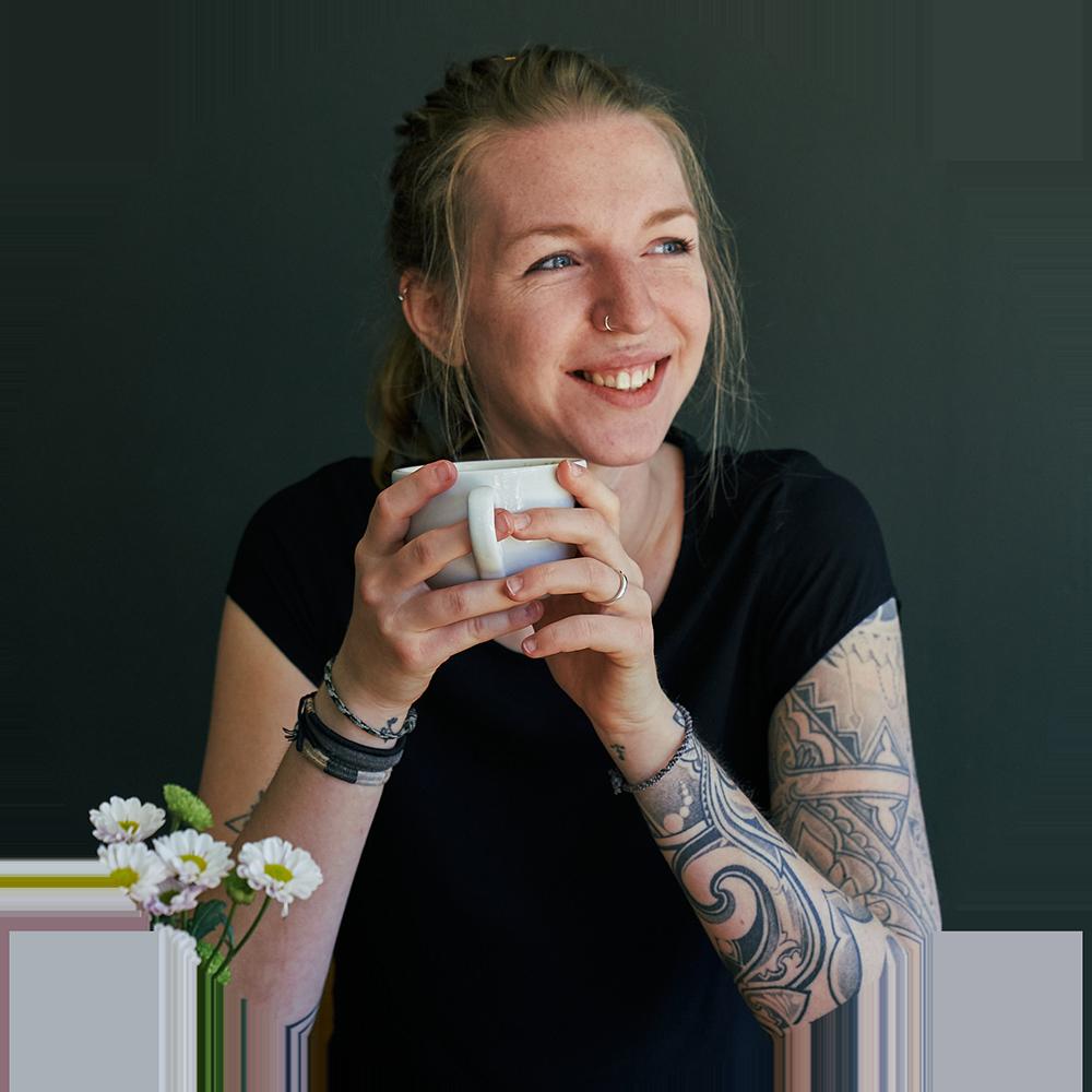 Frau mit Kaffeetasse vor grüner Wand