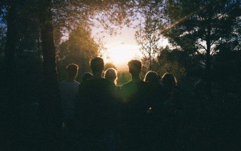 Junge Menschen in Wald mit Gegenlicht von Sonne