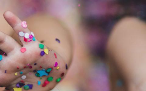 Mädchen mit Konfetti auf den Händen